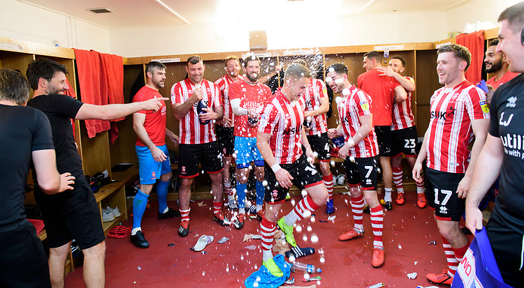 From left, Lincoln City manager Danny Cowley, Matt Gilks, Matt Rhead, Cian Bolger, Josh Vickers, Danny Rowe, Tom Pett, James Wilson, Neal Eardley, and Shay McCartan celebrate in the changing room after winning the league<br /> <br /> Photographer Chris Vaughan/CameraSport<br /> <br /> The EFL Sky Bet League Two - Lincoln City v Tranmere Rovers - Monday 22nd April 2019 - Sincil Bank - Lincoln<br /> <br /> World Copyright © 2019 CameraSport. All rights reserved. 43 Linden Ave. Countesthorpe. Leicester. England. LE8 5PG - Tel: +44 (0) 116 277 4147 - admin@camerasport.com - www.camerasport.com