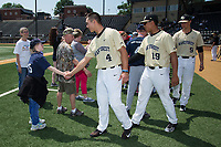 Wake Forest Demon Deacons players Stuart Fairchild (4), Christian Long (19), and Rayne Supple (9) shake hands with members of the Winston-Salem Miracle League prior to the game against the Pittsburgh Panthers at David F. Couch Ballpark on May 20, 2017 in Winston-Salem, North Carolina. The Demon Deacons defeated the Panthers 14-4.  (Brian Westerholt/Four Seam Images)