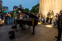 New York, NY 16 May 2015 - Pianist Colin Huggins playing piano under the arch on a rainy evening in Washington Square Park