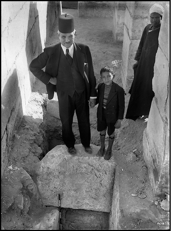 The people of the Ancient Empire...Access to the tombs of the dignitaries of the Ancient Empire by way of as many well shafts. Abdessalam Hussein brought his own son to visit the site, but made sure they were also accompanied by a rais, who enjoyed the spectacle as Taieb carefully recorded the scene for posterity on his glass photographic plates.....TAIEB HASSABOLLAH/COLLECTION PATRICK CHAPUIS-PHILIPPE FLANDRIN