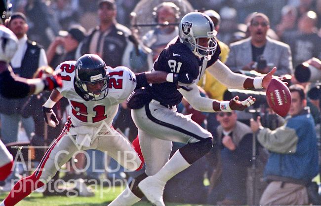 Oakland Raiders vs. Atlanta Falcons at Oakland Alameda County Coliseum Sunday, November 26, 2000.  Raiders beat Falcons  41-14.  Atlanta Flacons defensive back Elijah Williams (21) attempts to stop Oakland Raiders wide receiver Tim Brown (81).