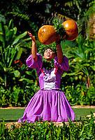 A beautiful hula dancer wearing a traditional dress chants with her ipu heke (gourd instrument) outdoors at Lanikuhonua on Oahu's leeward side.