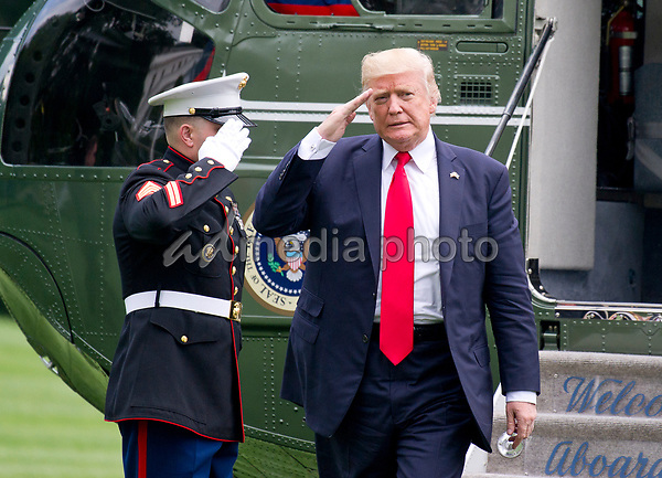 United States President Donald J. Trump salutes the Marine Guard as he arrives at the White House in Washington, DC following a trip from Miami, Florida on Friday, June 16, 2017.  In Miami, the President gave remarks and participated in a signing on the United Statesí policy towards Cuba. Photo Credit: Ron Sachs/CNP/AdMedia