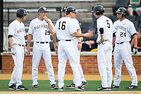 Wake Forest Demon Deacons head coach Tom Walter (16) talks with some of his players during the game against the Maryland Terrapins at Wake Forest Baseball Park on April 4, 2014 in Winston-Salem, North Carolina.  The Demon Deacons defeated the Terrapins 6-4.  (Brian Westerholt/Four Seam Images)