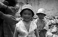 Two little kids react. Their first impression on seeing blond hair. While mother and other women build up the walls of a new home with small rocks. Tibet