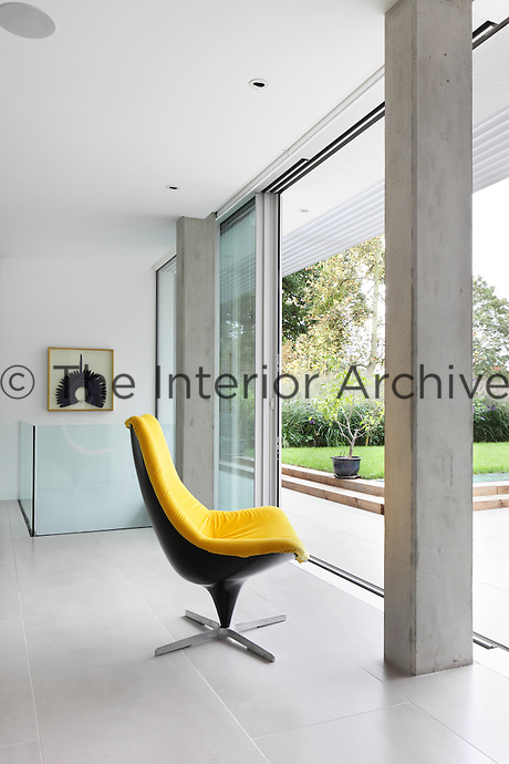 A spacious living room with full height glass sliding doors allowing access to the garden. A vibrant yellow chair provides an accent of colour against the otherwise white room.