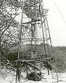 Doctor Robert H. Goddard's rocket is in the tower, ready for the July 17, 1929, test at Auburn, Massachusetts. This was the fourth flight of a liquid-propellant rocket. Rocks were piled on pipes directly under the nozzle, on a frame suspended from the two 3/8 inch pipe guides to keep the latter as straight as possible by the tension produced in this way. The noise from this particular rocket launch attracted the attention of the entire community.  When the public grew concerned over the potential hazards of the rockets, Goddard was forced to conduct his test flights on the Army artillery range at Camp Devens, Massachusetts..Credit: NASA via CNP
