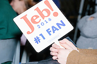 """A spectator holds a fan reading """"Jeb! 2016 #1 Fan"""" while Republican presidential candidate and former Florida governor Jeb Bush speaks at a town hall in Souhegan High School in Amherst, New Hampshire."""
