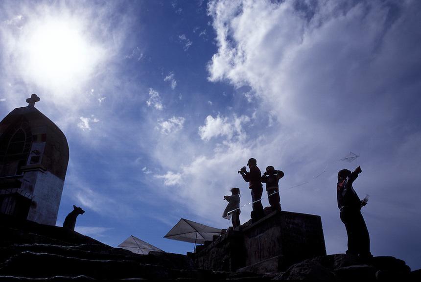 Children fly kites high above Lake Titicaca at the religious shrine of El Calvário, above Copacabana, Bolivia.