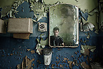 The reflection of a man in an old mirror with flaking paint