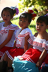 THREE SMALL MEXICAN GIRLS WAIT for THEIR PERFORMANCE at the FESTIVAL