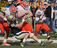 Syracuse center Macky MacPherson (59) and guard Zack Chibane (75) bowl over Pitt linebacker Max Gruder (55) allowing Syracuse running back Antwon Bailey (29) to score on a 26-yard touchdown reception. The Pittsburgh Panthers beat the Syracuse Orange 33-20 at Heinz Field in Pittsburgh, Pennsylvania on December 3, 2011