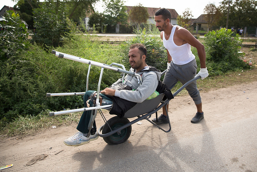 Horgos, Serbia-- September 15, 2015-- Massur Nasser Mohammed pushes his friend Gazi El Fadoudi (Faisal Hamad)along the road toward the Hungarian border, where on Tuesday, hundreds waited behind a closed gate. Mohammed, a champion distance runner from Aleppo. has been helping his friend, who was injured by an ISIS attack on his university, since the two met in Turkey. They were asking passersby for a pump to inflate the wheelbarrow's deflated tire.