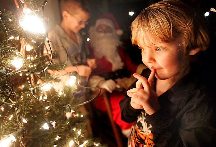 Five-year-old Brandon Jones searches for a candy cane from the tree as he and his family stopped at the Old Train Station to enjoy the festivities by BOLD. December 16, 2008.