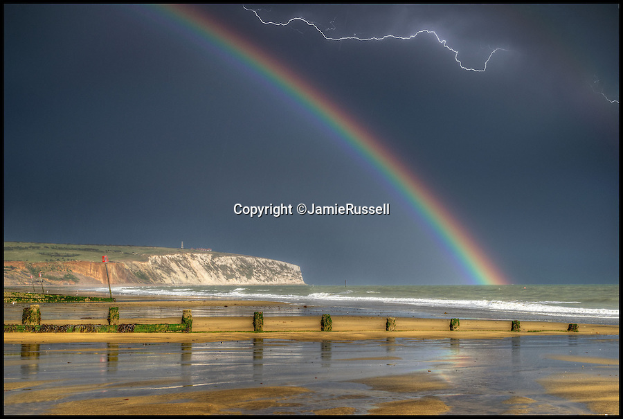BNPS.co.uk (01202 558833)<br /> Pic: JamieRussell/BNPS<br /> <br /> ***Please Use Full Byline***<br /> <br /> Storm chaser photographer Jamie Russell captures a lightning flash and a rainbow over Culver on the Isle of Wight.
