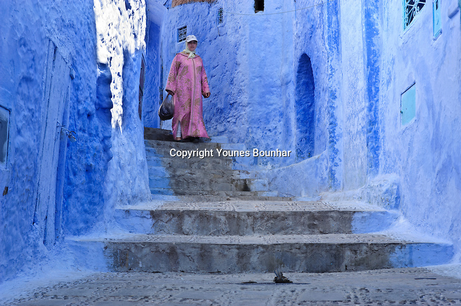 A woman ina pink djellaba walks down the stairs in the mesmerizing blue streets of Chefchaouen (at the foot of the Rif mountains of Morocco)
