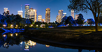 Houston cityscape pano along the Buffalo Bayou near the Police Memorial after dark in downtown part of city.  We like the Houston skyline  from this location which run along the Buffalo Bayou and gives off a nice reflection from the city and the trail lights giving off a faint blue glow among the trees and in the bayou with the fantastic cityscape in the background. Houston has some of the tallest buildings in Texas and the southwestern US so you can be miles from downtown and still see them.