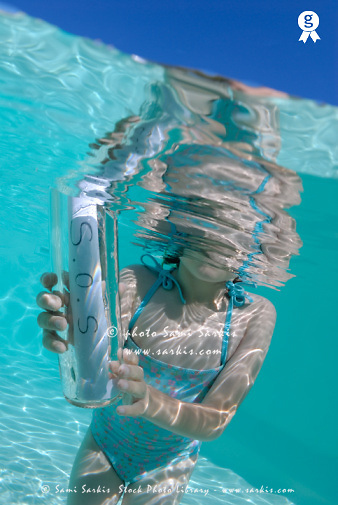 Girl (6-7) in pool holding bottle with SOS message (Licence this image exclusively with Getty: http://www.gettyimages.com/detail/sb10069714bo-001 )