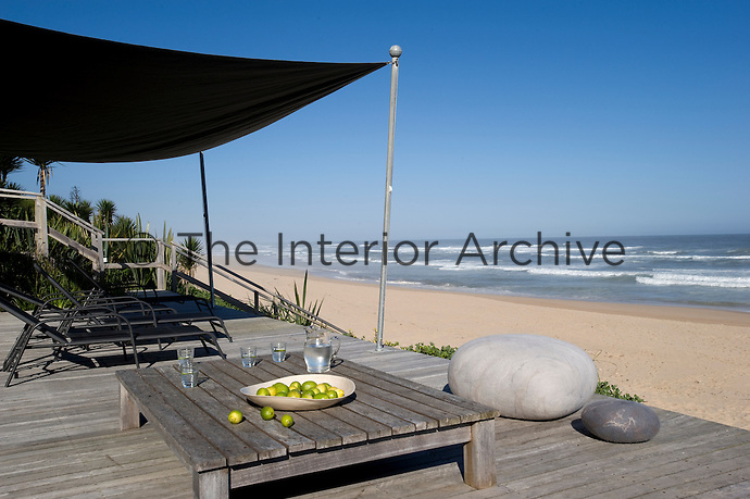 A canopy provides shade for this simple decked terrace which has unrestricted views of the ocean