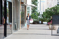 Attractive female business woman shopper with shopping bags walks down the sidewalk at an Austin outdoor shopping center
