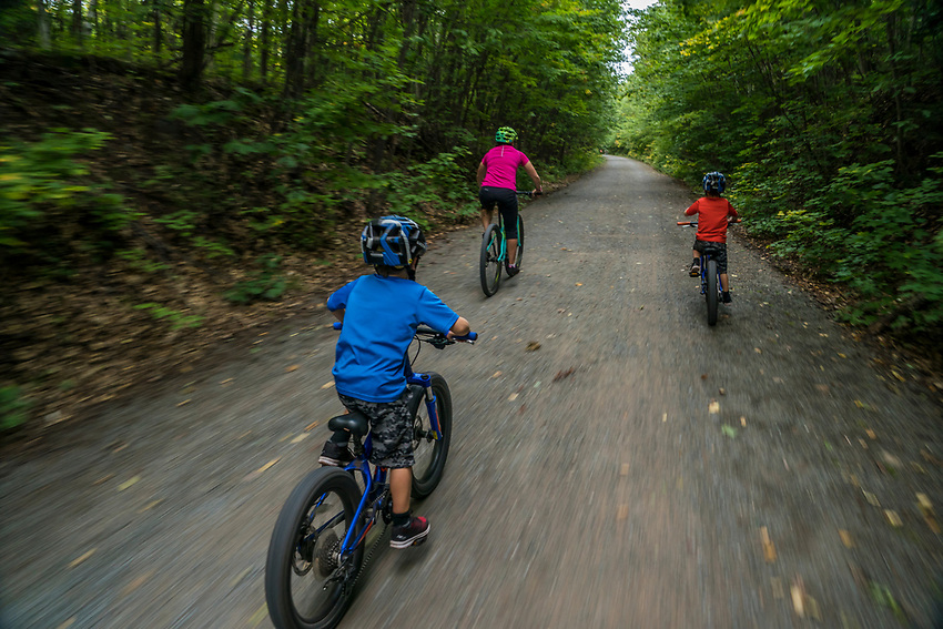 A young family bikes along the Iron Ore Heritage Trail near Marquette, Michigan. The IOHT follows a former railroad corridor that linked the iron mining commuties of Marquette County with the Lake Superior shipping port in the city of Marquette.