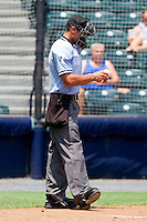 Home plate umpire Joey Amaral checks a baseball to see if can stay in play during the Eastern League game between the Harrisburg Senators and the Richmond Flying Squirrels at The Diamond on July 22, 2011 in Richmond, Virginia.  The Squirrels defeated the Senators 5-1.   (Brian Westerholt / Four Seam Images)