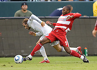 LA Galaxy midfielder David Beckham is tackled by FC Dallas forward Jeff Cunningham. The LA Galaxy defeated FC Dallas 2-1 at Home Depot Center stadium in Carson, California on Sunday October 24, 2010.