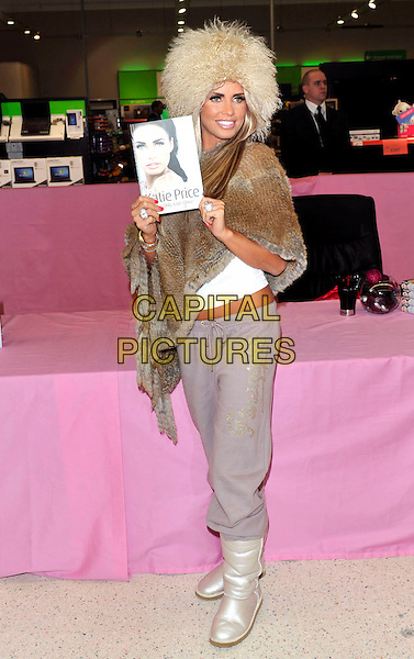 "KATIE PRICE (JORDAN).""You Only Live Once""  book signing at Asda Superstore (supermarket), Milton Keynes, Buckinghamshire, England 3rd February  2011.full length beige gold silver shawl wrap fur hat white ugg boots tracksuit bottoms poncho .CAP/ROS.©Steve Ross/Capital Pictures"
