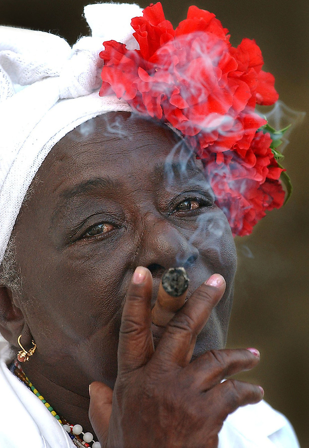 04/11/2004:  Journal photo by Ted Richardson:  A practitioner of Santeria, a religion with African roots, enjoys her cigar near the Plaza of the Cathedral in Old Havana.