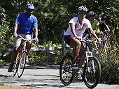 First Lady Michelle Obama rides a bike with daughter Sasha Obama (off camera) and a security detail on a bike path through Manuel F. Correllus State Forest in West Tisbury, Massachusetts while vacationing on Martha's Vineyard on August 23, 2011.   .Credit: Matthew Healey / Pool via CNP