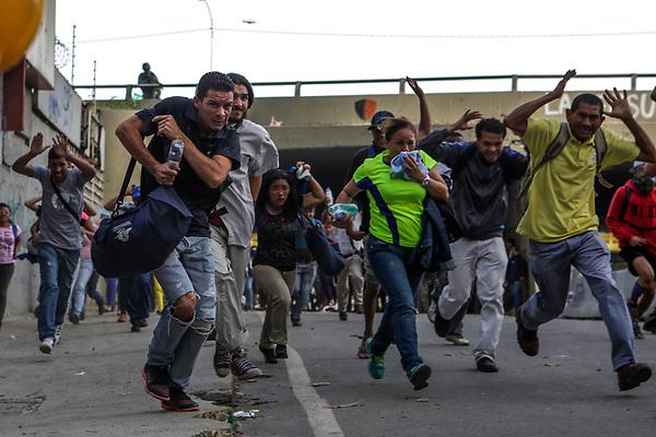 """CAR28. CARACAS (VENEZUELA), 10/07/2017.- Transeúntes corren para alejarse de los enfrentamientos entre manifestantes opositores y la Guardia Nacional Bolivariana (GNB) durante el """"trancazo"""" de hoy, lunes 10 de julio de 2017, en Caracas (Venezuela). Manifestantes opositores y efectivos de la Guardia Nacional Bolivariana (GNB) se enfrentaron hoy en varios puntos de Caracas durante un nuevo corte de calles masivo convocado por la oposición en todo el país para protestar contra el proceso Constituyente impulsado por el Gobierno de Nicolás Maduro. EFE/Cristian Hernández"""