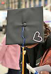 Manhattan, New York, U.S. - May 21, 2014 - On 7th Avenue, a young man who graduated from Pace University that day tilts his head to show the top of his black graduation mortar board hat, which is decorated with a rhinestone pink heart, during a pleasant Spring day in Manhattan. A blue and gold tassel topper is handing from the hat.