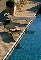 A pair of contemporary sun-loungers graces the wooden decking which surrounds an outdoor swimming pool