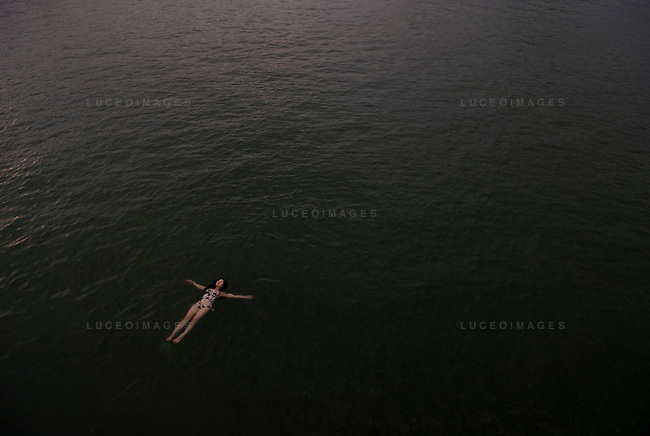 A tourist relaxes in the waters of Ha Long Bay, Vietnam.