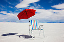 Bolivia, Altiplano, empty camping chair with umbrella in Salar de Uyuni, world's largest salt pan