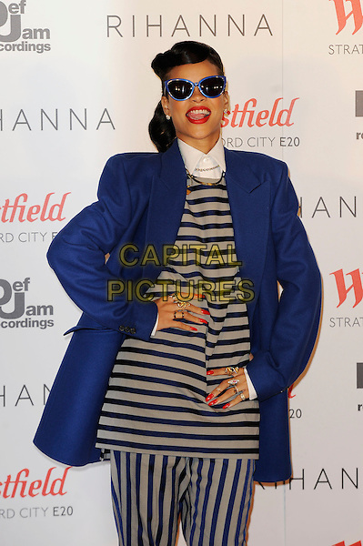 Rihanna (Robyn Rihanna Fenty).switches on the Westfield Stratford City Christmas Lights, Stratford, London, England..19th November 2012.half length coat jacket  sunglasses shades white collar blue grey gray stripe top trousers red lipstick nail varnish polish hands on hips mouth open  tongue .CAP/MAR.© Martin Harris/Capital Pictures.