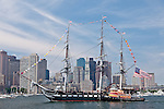 The USS Constitution passes the Boston skyline on her annual Turnaround Cruise on July 4th in Boston Harbor, Boston, MA, USA