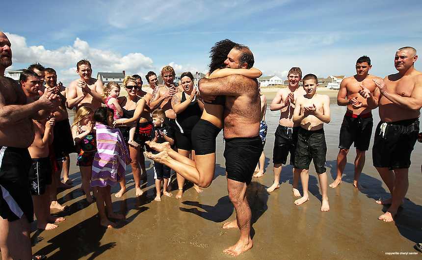 After the group, supporters of Chucky's Fight, takes a fundraising plunge into the ocean, Chuck Rosa, right, of Seabrook hugs Dianne Chalifour, left, of Portsmouth, in Seabrook, N.H., Sunday, April 1, 2012.  (Portsmouth Herald Photo Cheryl Senter)