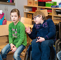 Non-disabled and disabled students (in this case a boy in a wheel chair) learn together in the same class in a primary school.