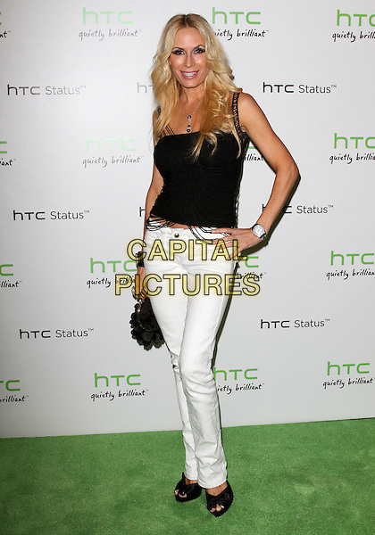 Peggy Tanous .The HTC Statusª Social Launch Event held at Paramount Studios in Hollywood, California, USA..July 19th, 2011.full length black white top jeans denim hand on hip shirt clutch bag.CAP/ADM/KB.©Kevan Brooks/AdMedia/Capital Pictures.