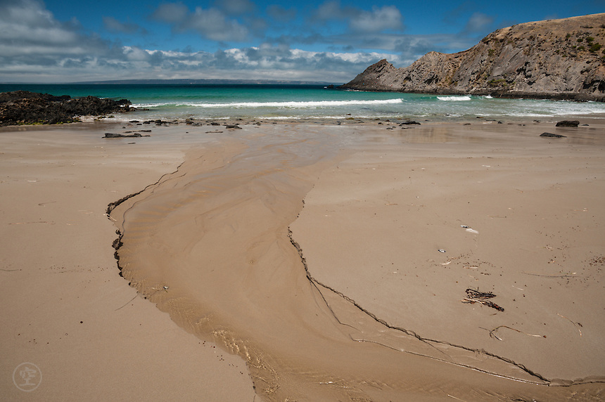 Blowhole Creek meets the ocean on a sandy beach at Deep Creek Conservation Park, South Australia.