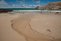 Blowhole Creek meets the ocean on a sandy beach at Deep Creek Conservation Park, South Australia.