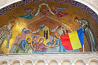"Romania. Iași County. Iasi. Religious scenery and Romanian flag above the entrance to  the Orthodox Church ""Saint Nektarios"". The national flag of Romania is a tricolor with vertical stripes, beginning from the flagpole: blue, yellow and red. Iași (also referred to as Iasi, Jassy or Iassy) is the largest city in eastern Romania and the seat of Iași County. Located in the Moldavia region, Iași has traditionally been one of the leading centres of Romanian social, cultural and artistic life. The city was the capital of the Principality of Moldavia from 1564 to 1859, then of the United Principalities from 1859 to 1862, and the capital of Romania from 1916 to 1918. 6.06.15 © 2015 Didier Ruef"