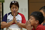 Deaconess Irene Lagahit Vioya leads a group of children in prayer before a meal in Knox United Methodist Church in Manila, Philippines. She is a graduate of Harris Memorial College.