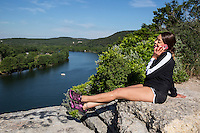 Beautiful African-American woman talking on her smartphone sits on a cliff overlooking Lake Austin, Texas.