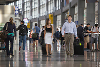 View of businessman and businesswoman walking through the Austin–Bergstrom International Airport (ABIA) terminal on a business trip.