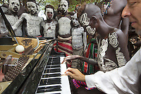 "Ethiopia. Southern Nations, Nationalities, and Peoples' Region. Omo Valley. Korcho Village. Kara tribe. Agro-pastoralist group. The Kara men are best known for the elaborate body painting they indulge in before important ceremonies. They paint their faces and bodies in white chalk. Marc Vella is a french musician and a nomadic pianist. Over the last 25 years he has travelled with his Grand Piano in around forty countries to celebrate humanity. Thanks to the variacordes which he has devised, his piano music is unique. Creator of ""La Caravane amoureuse"" (The Caravan of Love) he takes people with him to say ""I love you"" to others and ""lovingly conquered"" their hearts and souls. Marc Vella and a Karo boy play an improvised duet-playing - one piano and four hands. The Omo Valley, situated in Africa's Great Rift Valley, is home to an estimated 200,000 indigenous peoples who have lived there for millennia. Amongst them are 1,000 to 2,000 Karo who dwell on the eastern banks of the Omo river. Southern Nations, Nationalities, and Peoples' Region (often abbreviated as SNNPR) is one of the nine ethnic divisions of Ethiopia. 8.11.15 © 2015 Didier Ruef"