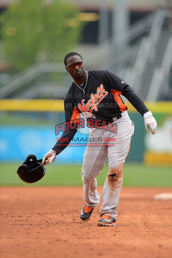 Norfolk Tides outfielder Trayvon Robinson #25 tosses his helmet to the bench in between innings during a game against the Buffalo Bisons on May 9, 2013 at Coca-Cola Field in Buffalo, New York.  Norfolk defeated Buffalo 7-1.  (Mike Janes/Four Seam Images)