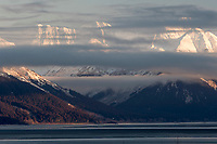 winter landscape shows wisps of clouds shroud the Chugach Mountains that jut above Turnagain Arm  January 2014
