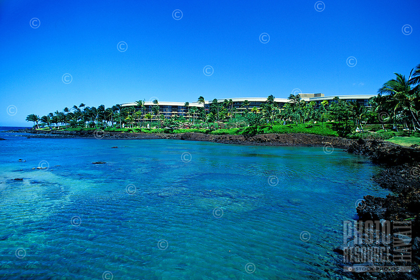 The Hilton Waikaloa village resort shot from the ocean, with black lava and palm trees fronting the resort.